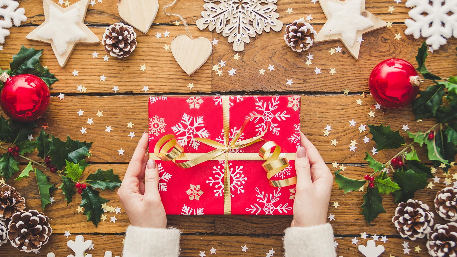 Woman hands holding Christmas present laid on a wooden table bac